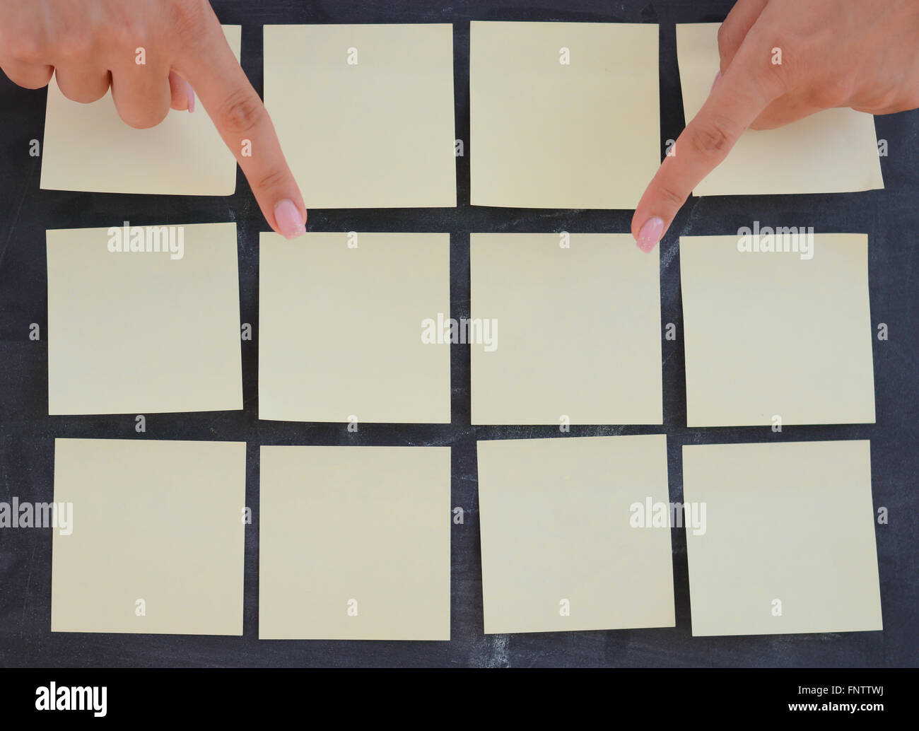 Woman hand posting empty adhesive notes on blackboard - Stock Image