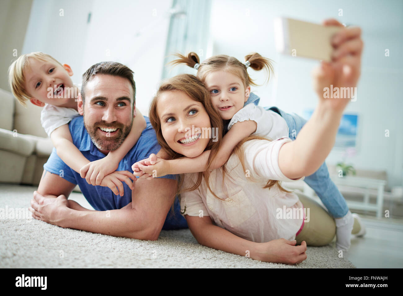 Happy young family taking selfie on the floor at home - Stock Image