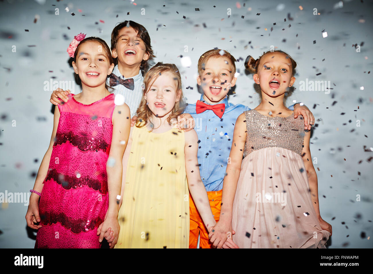 Group of happy children standing under falling confetti - Stock Image
