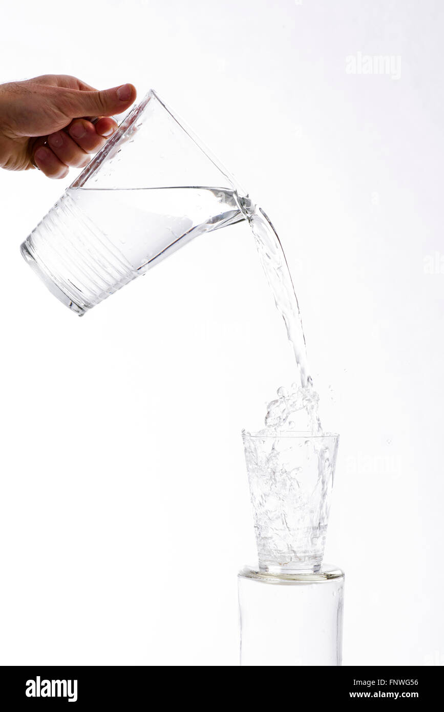Water, vigorously poured from a jug overflowing splashing from a glass, on a white background - Stock Image