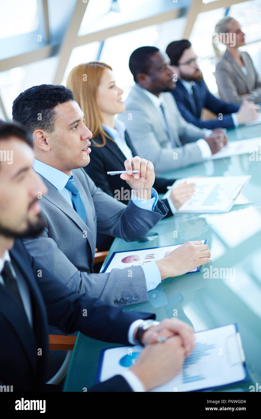 Businessman and his colleagues attending business seminar - Stock Image