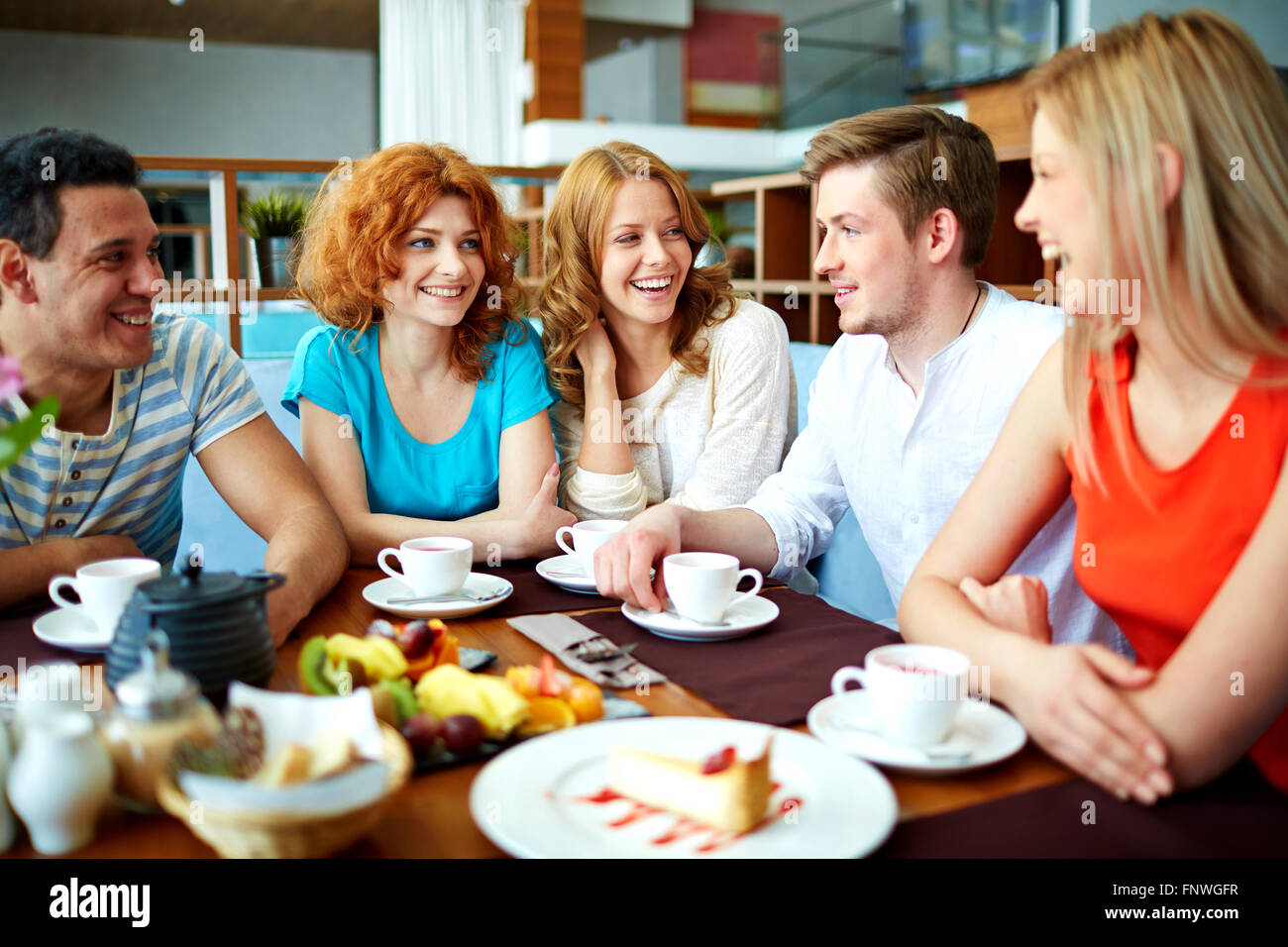 Happy teenage friends having talk by cup of tea in cafe - Stock Image