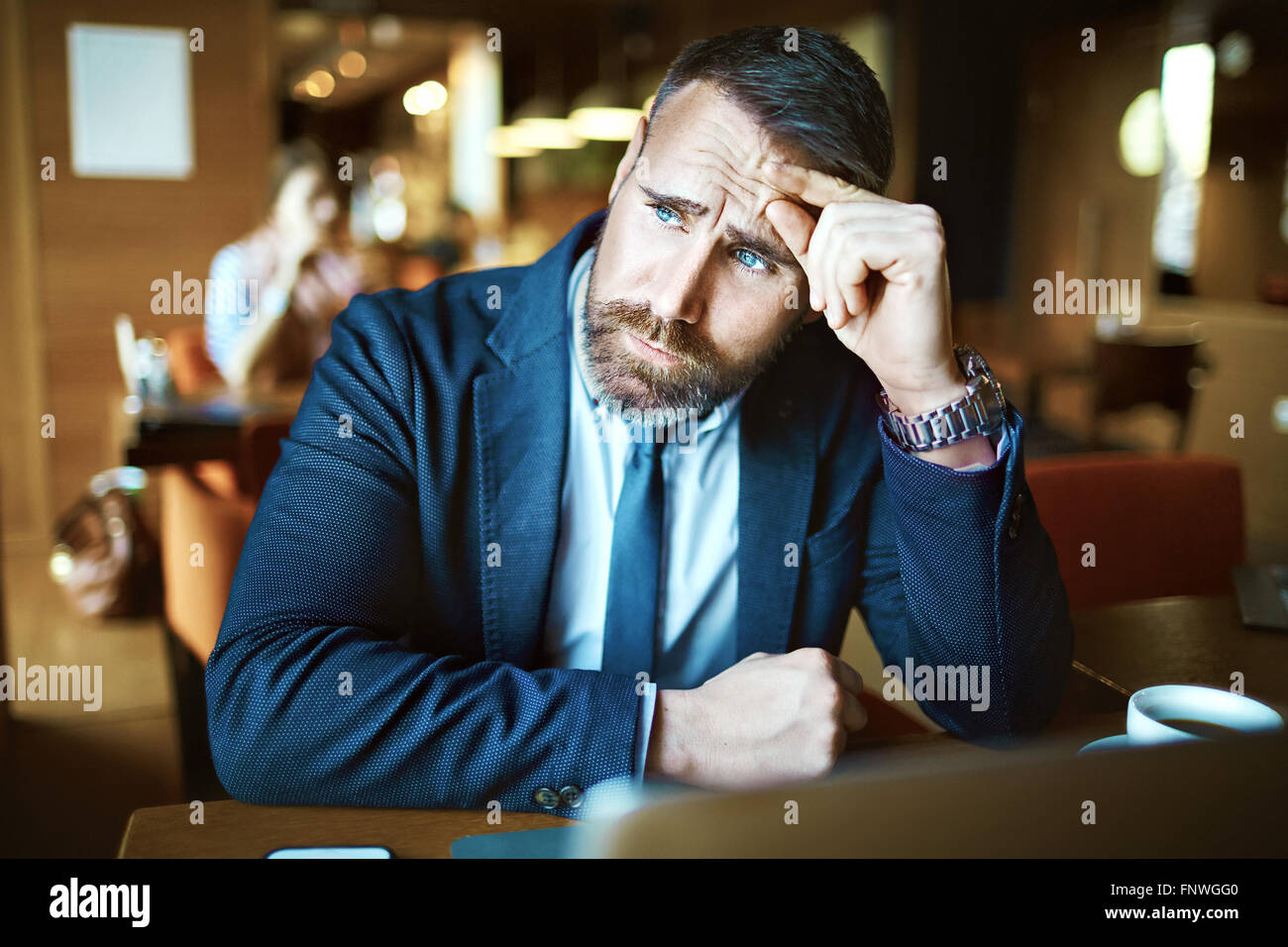 Pensive man touching his forehead and looking sideways - Stock Image