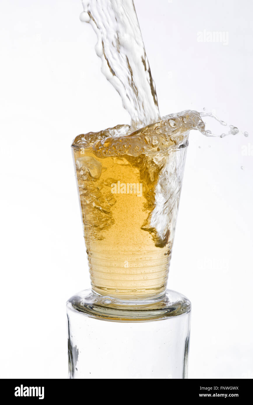 Tea drinks poured vigorously overflowing splashing from a glass, on a white background - Stock Image