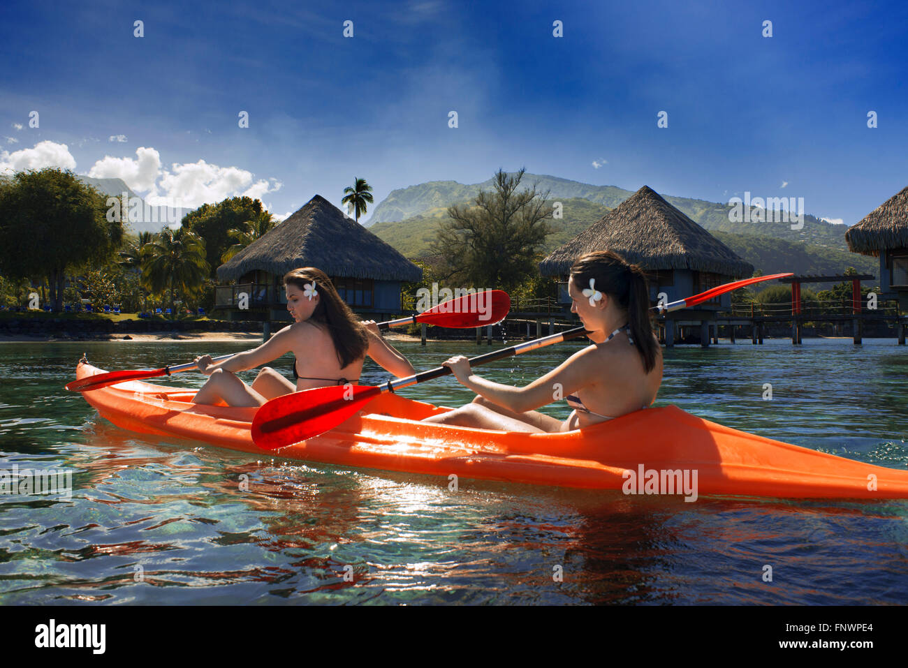 Two nice girls doing kayak in front of Meridien Hotel on the island of Tahiti, French Polynesia, Tahiti Nui, Society - Stock Image