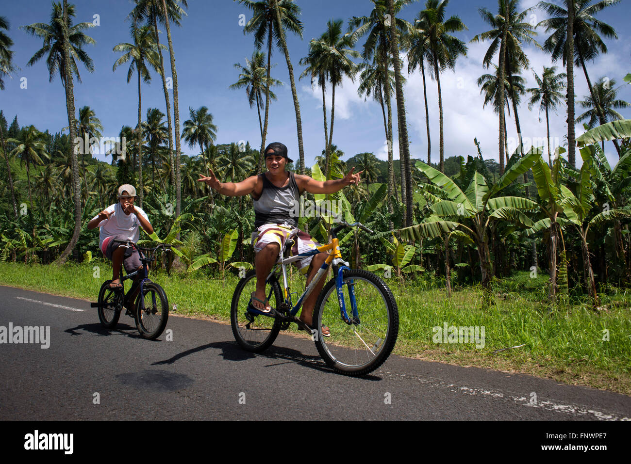 Palm trees and teen boys cyclists at Route de ceinture, Tahiti Nui, Society Islands, French Polynesia, South Pacific. - Stock Image