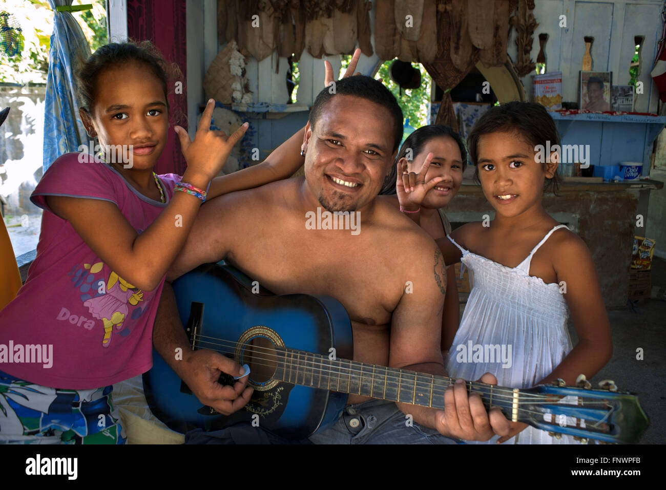 Inside of a traditional house in Rangiroa, Tuamotus Islands, French Polynesia, South Pacific. Man playing guitar - Stock Image