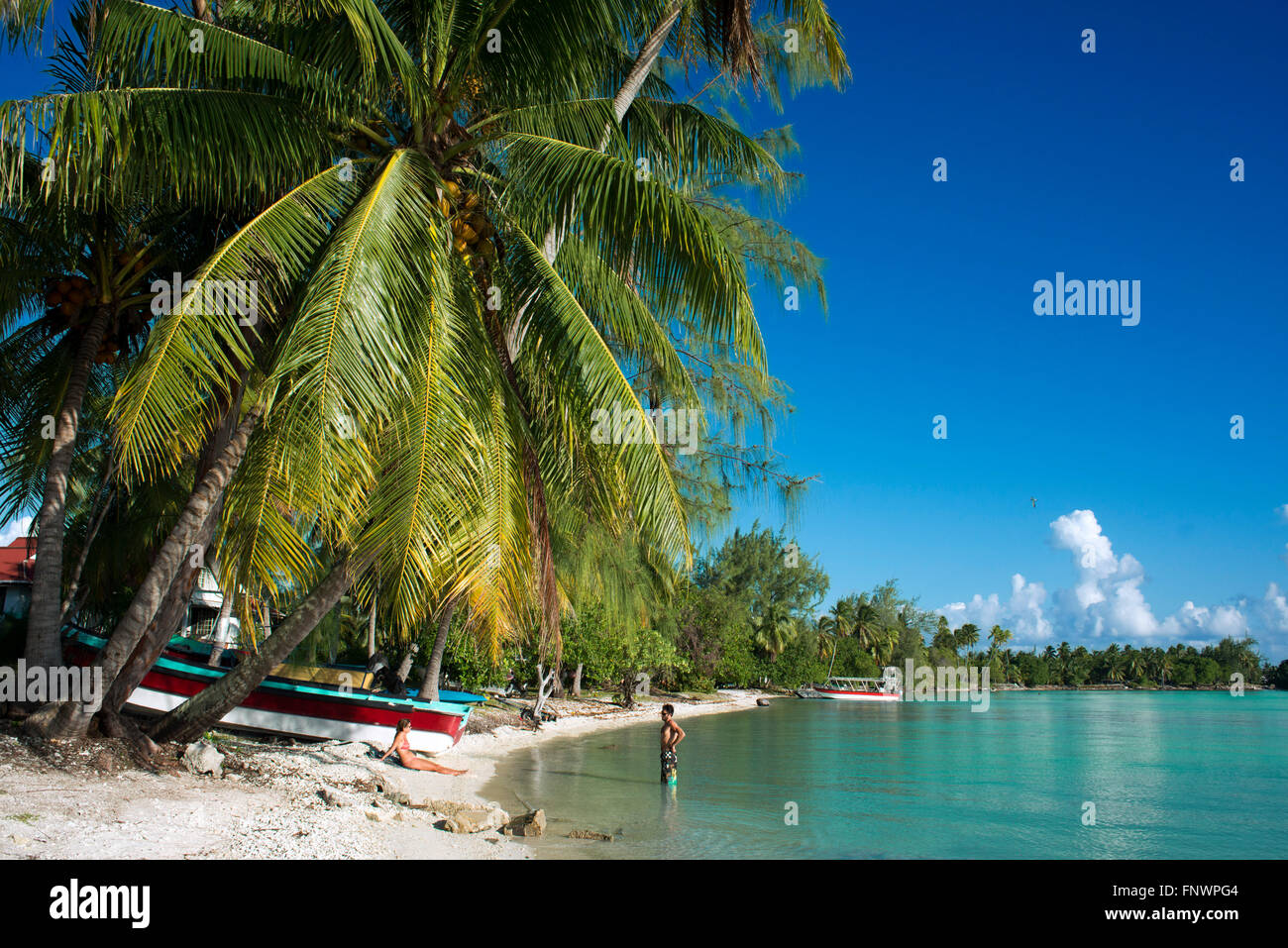 A couple relaxes in the beach of Rangiroa, Tuamotu Islands, French Polynesia, South Pacific. - Stock Image