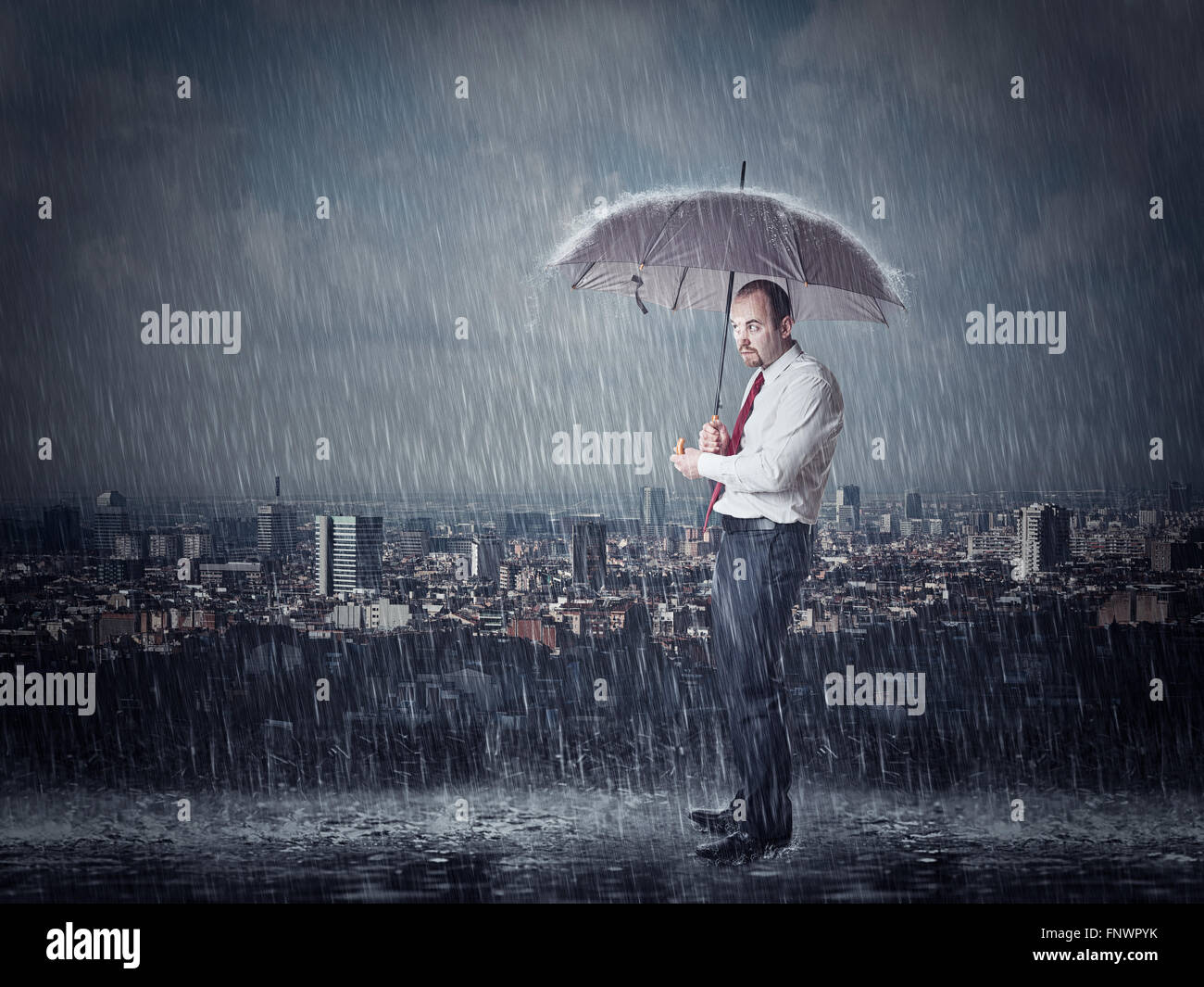 man with umbrella and heavy rain urban background - Stock Image