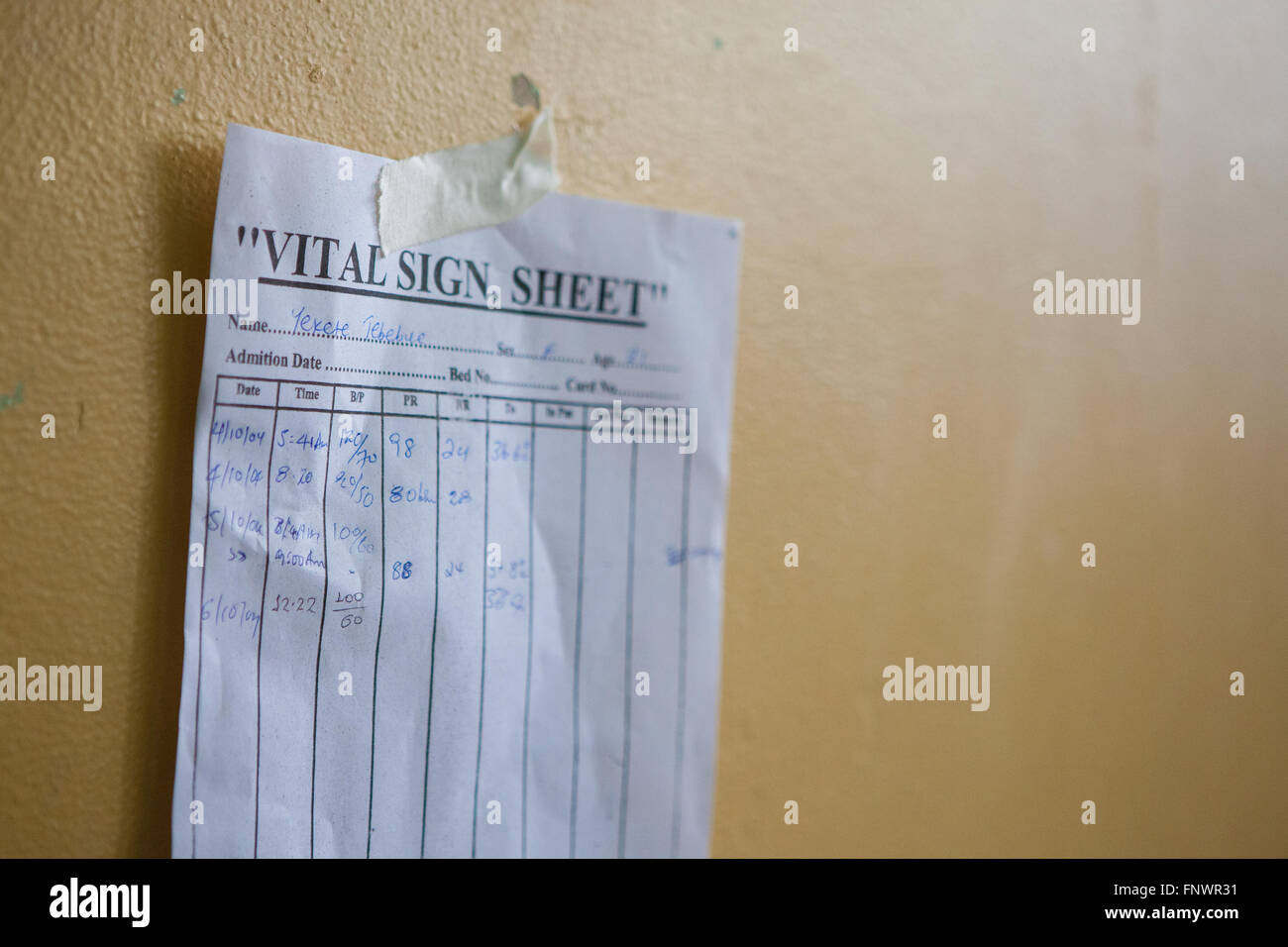 A Patients Vital Sign Sheet Taped To The Wall Above Her Hospital