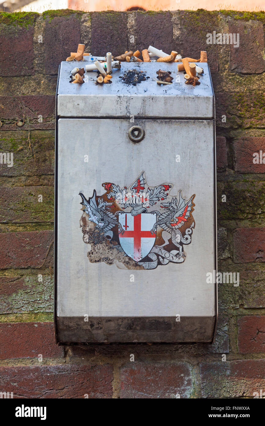 A wall-mounted receptacle for cigarette ends, complete with the much-worn City  of London coat of arms, in a City - Stock Image