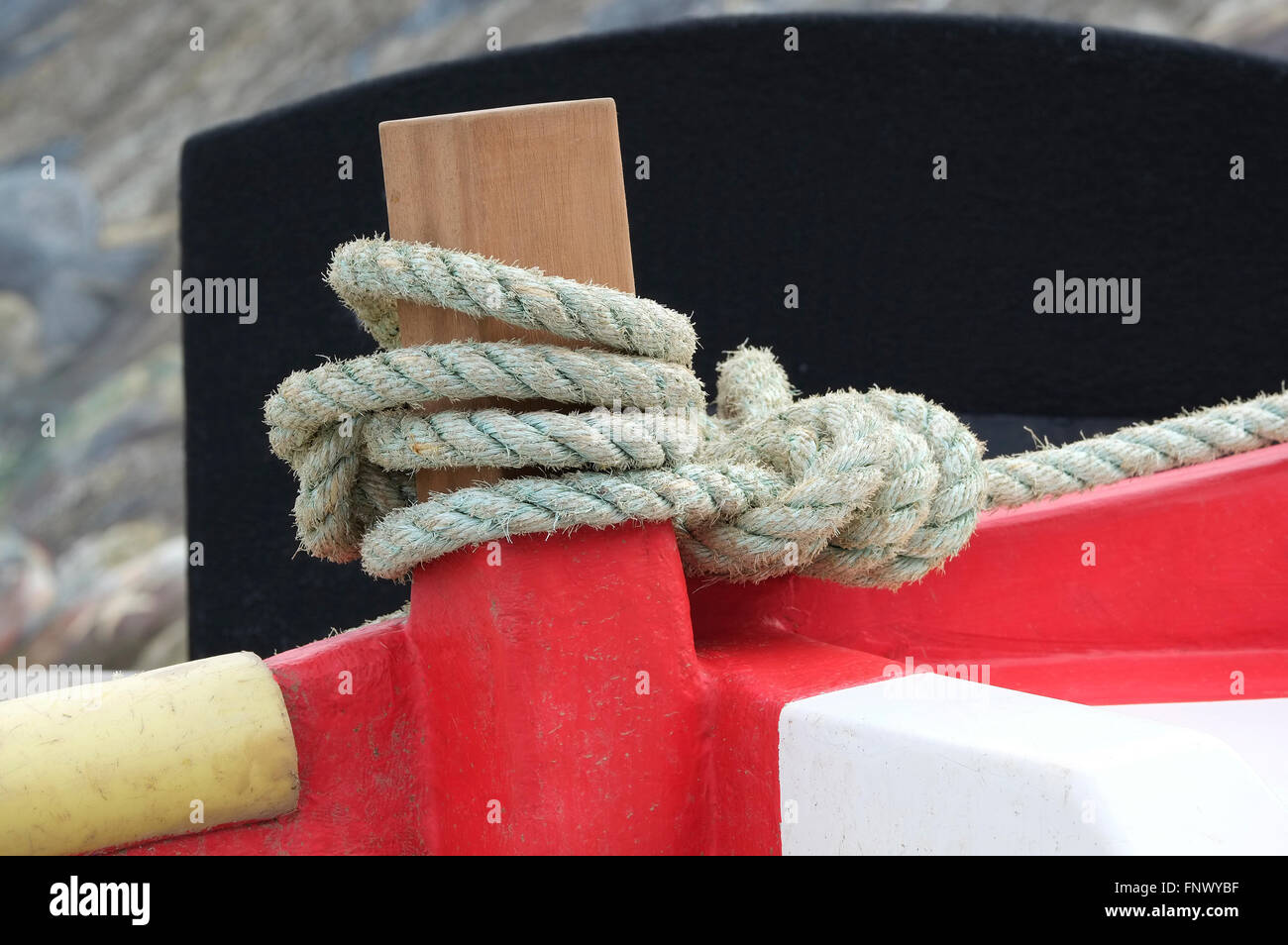 rope tied to fishing boat stantion stanchion post - Stock Image