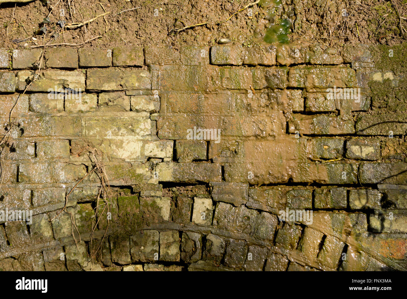 Crumbling brick wall with water running down. - Stock Image