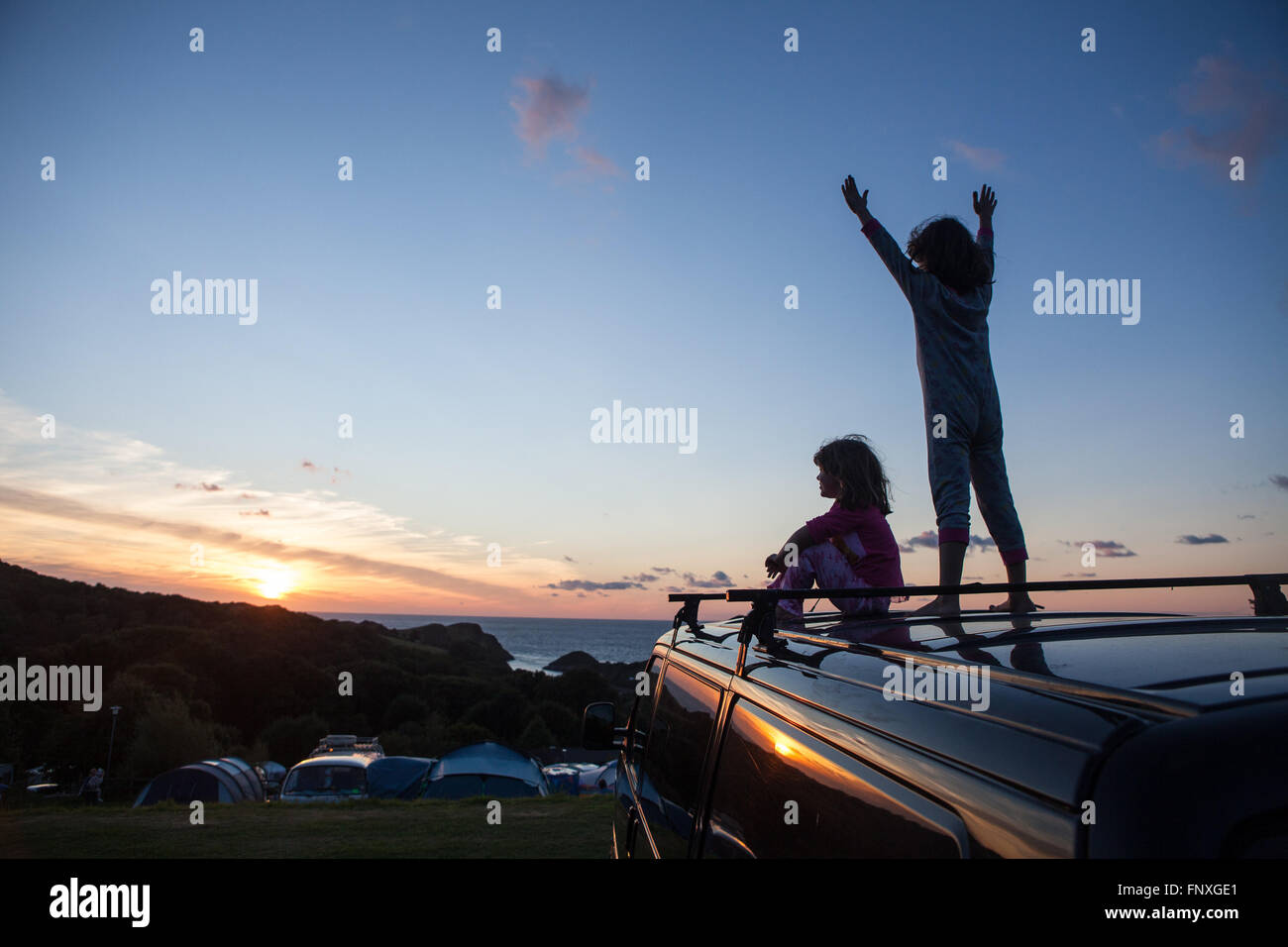 Two young children watch the sunset on a camping holiday. Childhood memories are made on camping holidays by the - Stock Image
