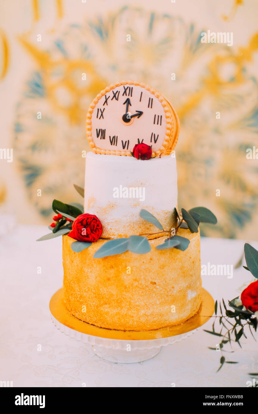Wedding cake decorated with clocks and flowers close up - Stock Image