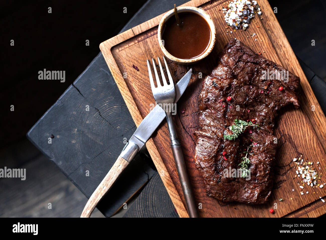 Beefsteak. Piece of grilled BBQ beef marinated in spices and herbs on rustic wooden board over rough wooden desk - Stock Image
