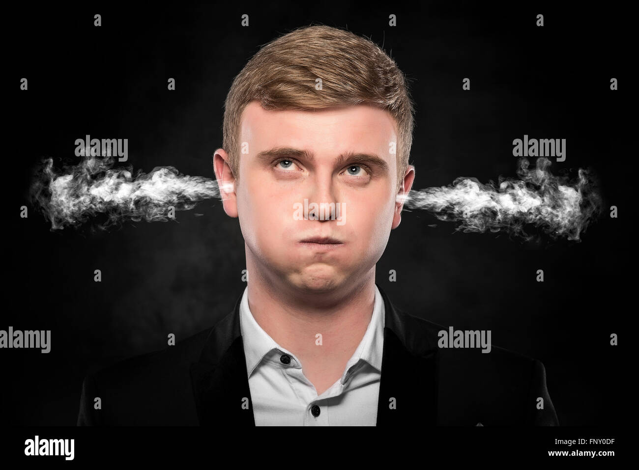 Stressful man with smoke coming out from his ears. - Stock Image