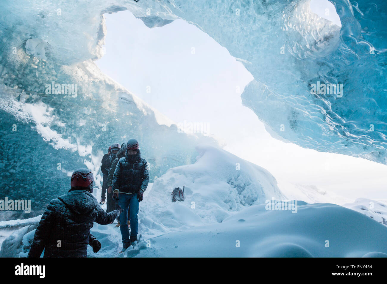 People at the entrance of an ice cave, Vatnajökull Nationalpark, Glacier, Iceland - Stock Image