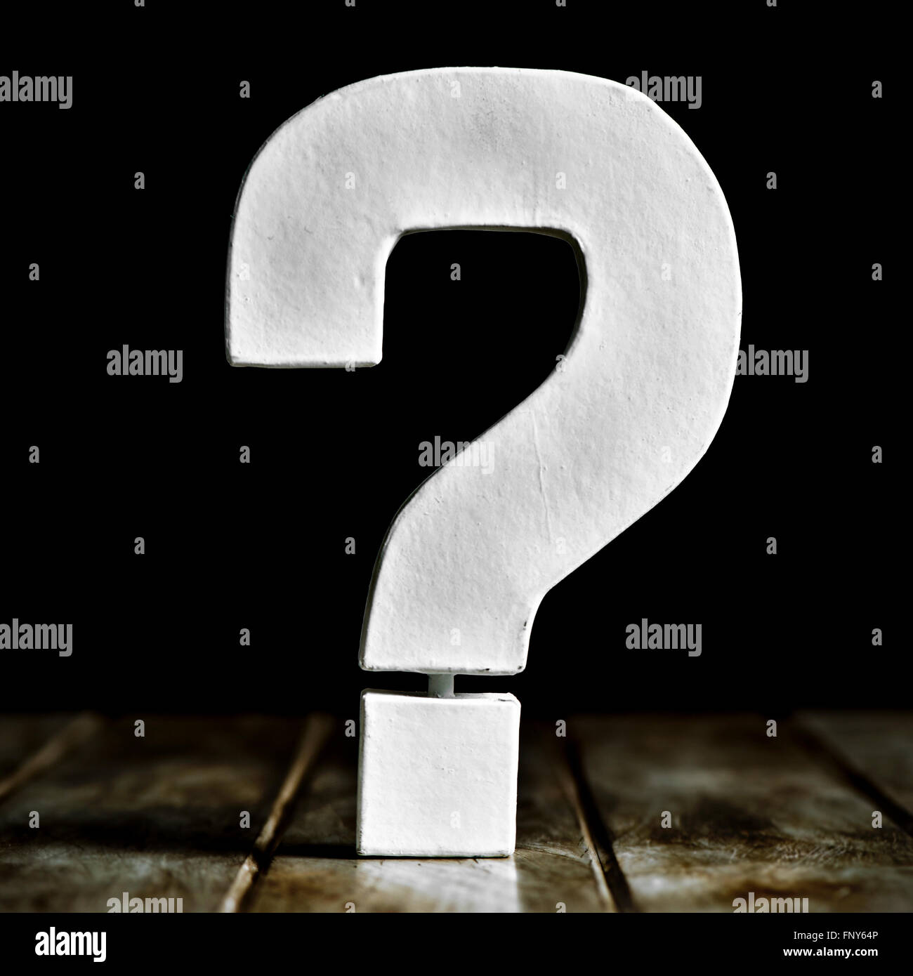 a white three-dimensional question mark on a rustic wooden surface against a black background - Stock Image