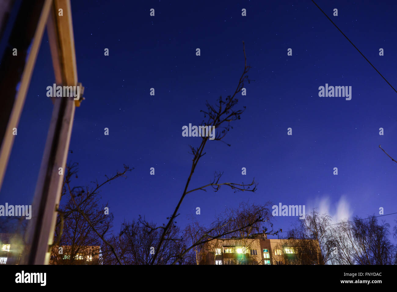 The starry sky and the moon over the buildings. View from my window. Moon and star dust in the sky. - Stock Image