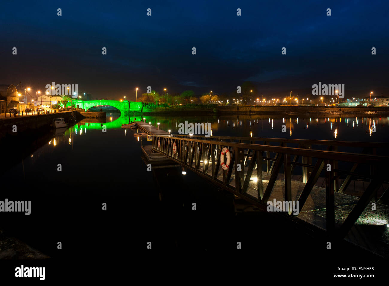 The Devonshire Bridge, lit up green for Saint Patrick's Day, reflected on the water of Dungarvan Harbour, Waterford, - Stock Image