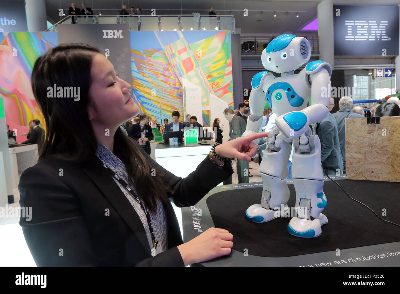 A stand hostess touches a NAO Watson robot at the IBM stand at the 2016 CeBIT digital technology trade fair in Hannover, - Stock Image
