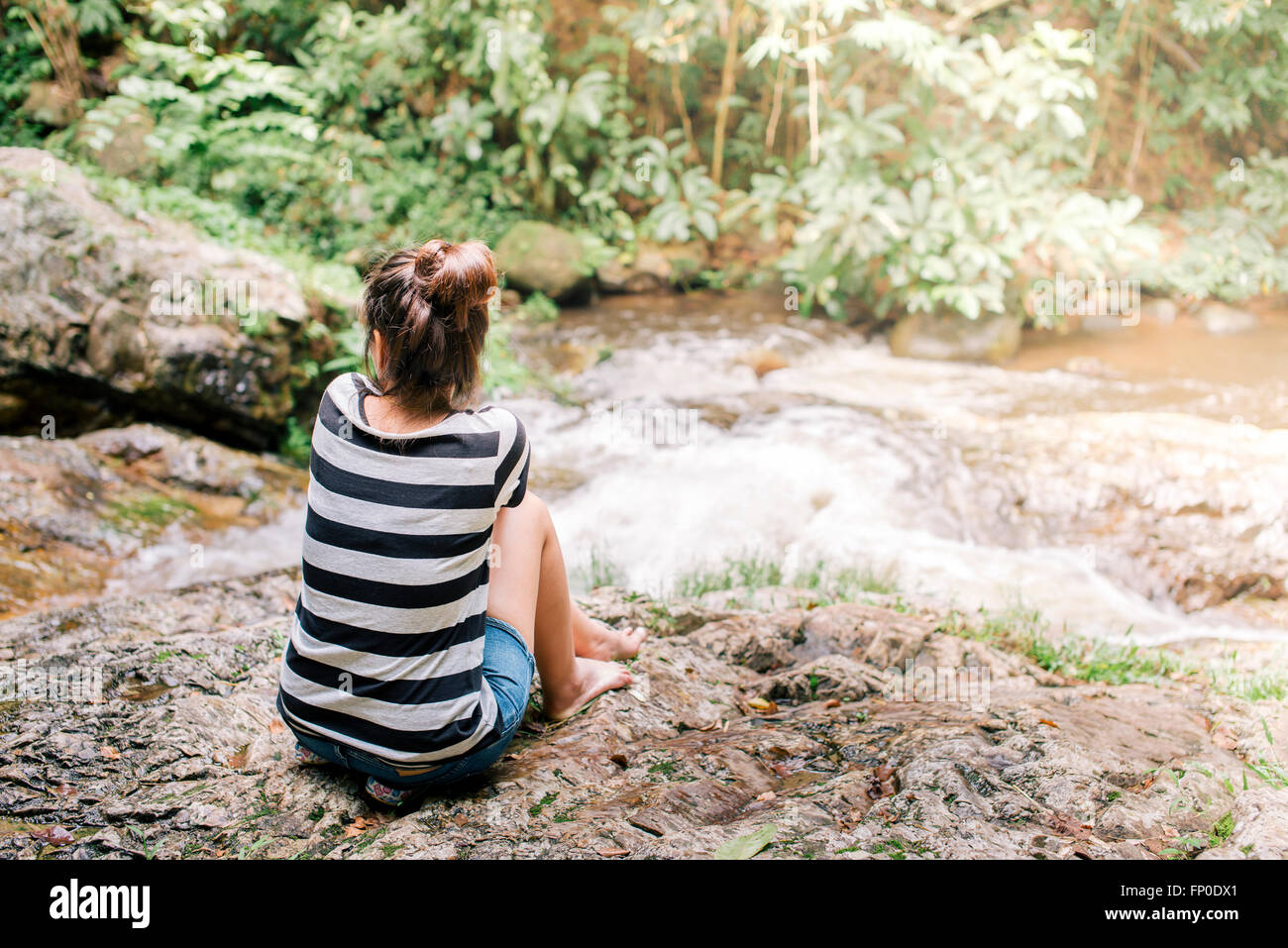 Relaxing concept, Woman sitting nearby waterfall. Film tone - Stock Image