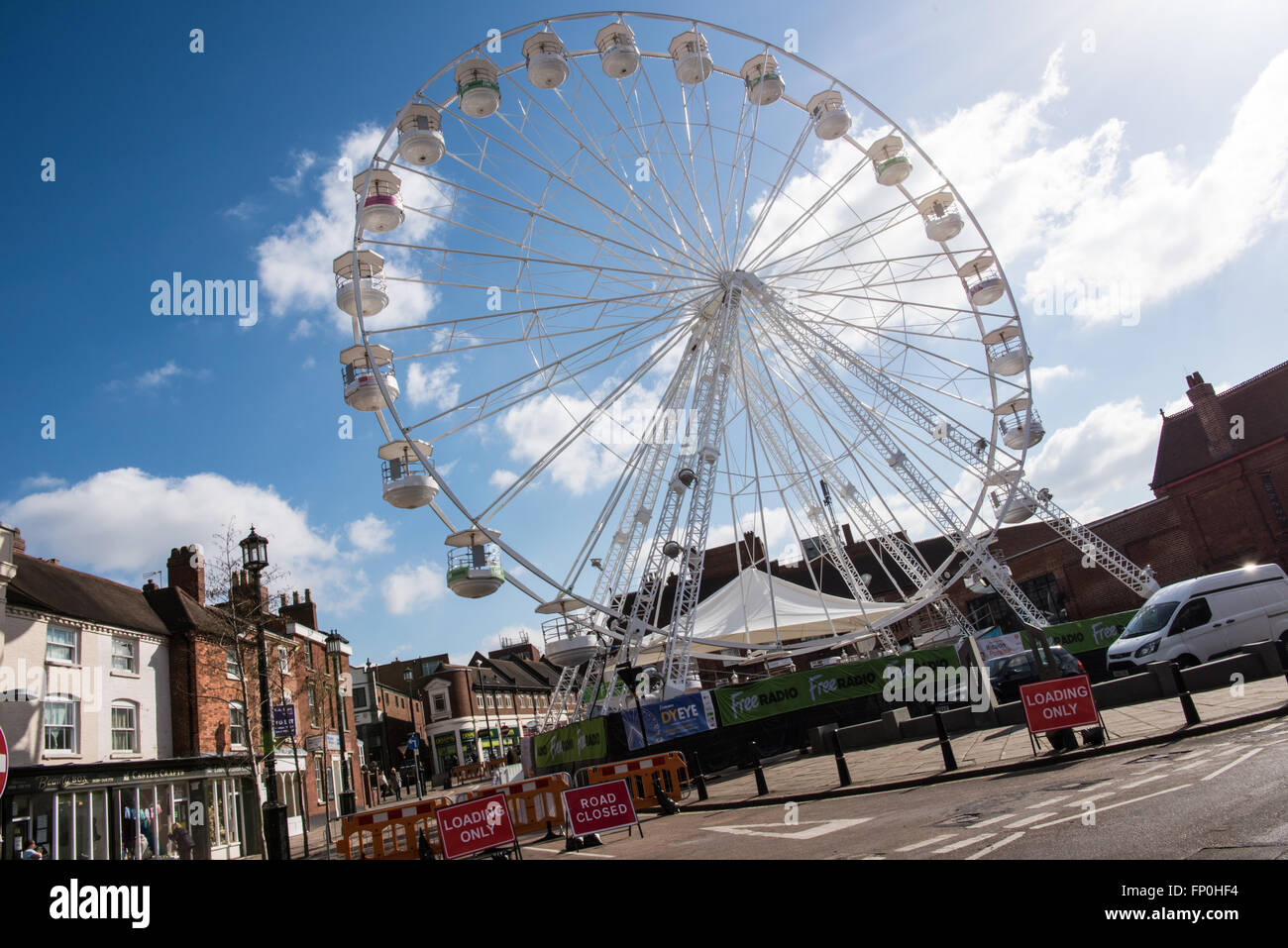 View of a large ferris wheel in historic Dudley town centre on a sunny day. It was a council bid to encourage visitors - Stock Image