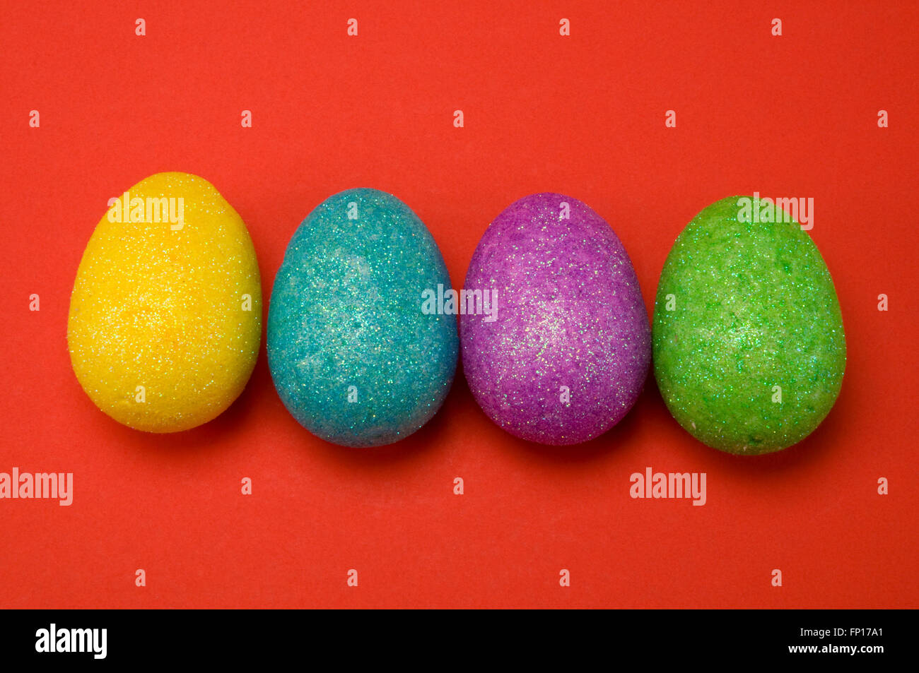 Sparkle Easter eggs on red - Stock Image