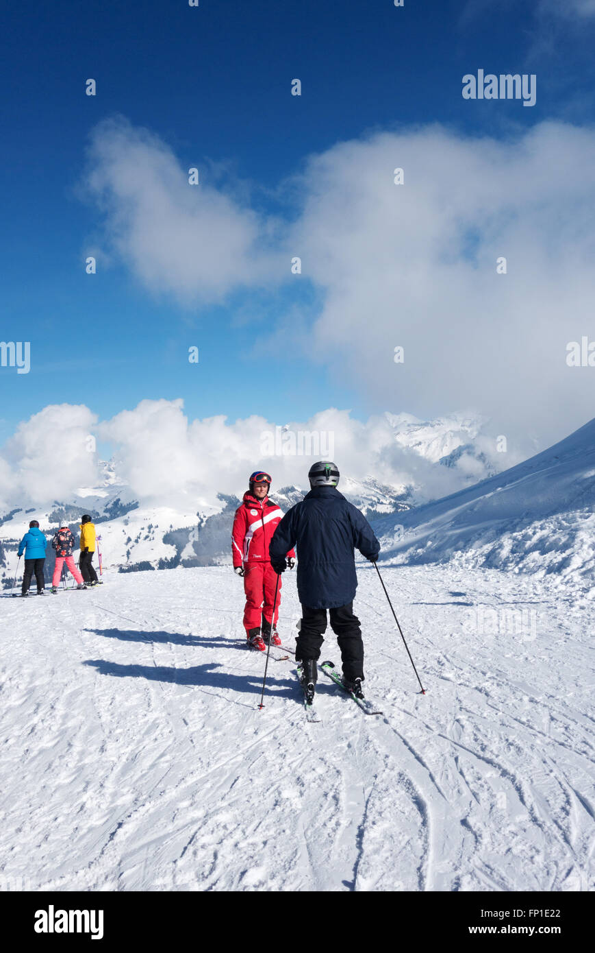 An adult (in black), having a skiing lesson from an instructor (in red), the Alps, Lenk, Canton of Bern, Switzerland, - Stock Image