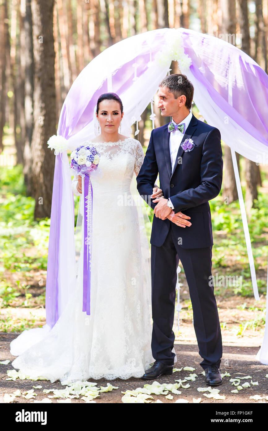 Bride and Groom Under wedding arch Stock Photo