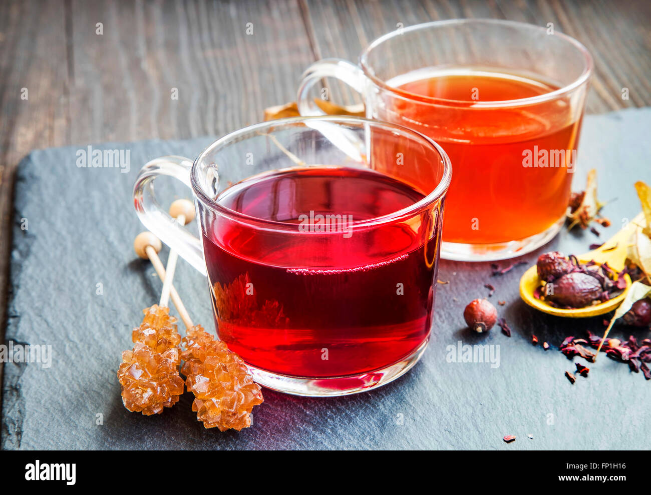Red berries tea in transparent cups with brown sugar rock candy and dried flowers and fruits - Stock Image