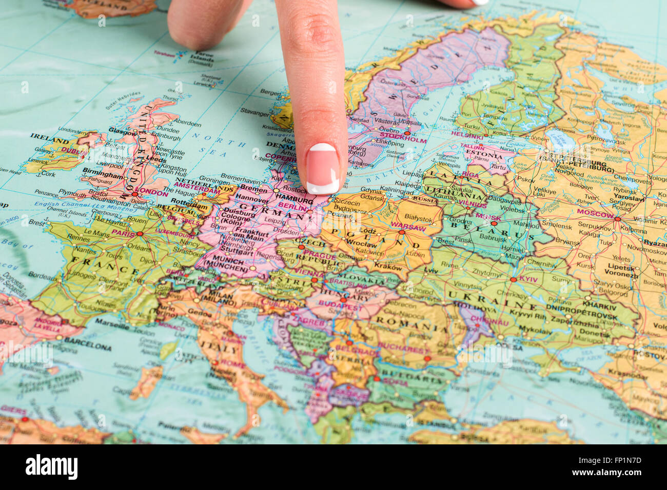 Germany in atlas. Woman's finger shows Germany's borders. Home of the finest beer. Member of European Union. - Stock Image