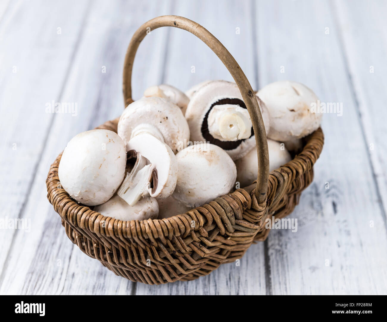 Portion of fresh white Mushrooms (selective focus) on wooden background - Stock Image