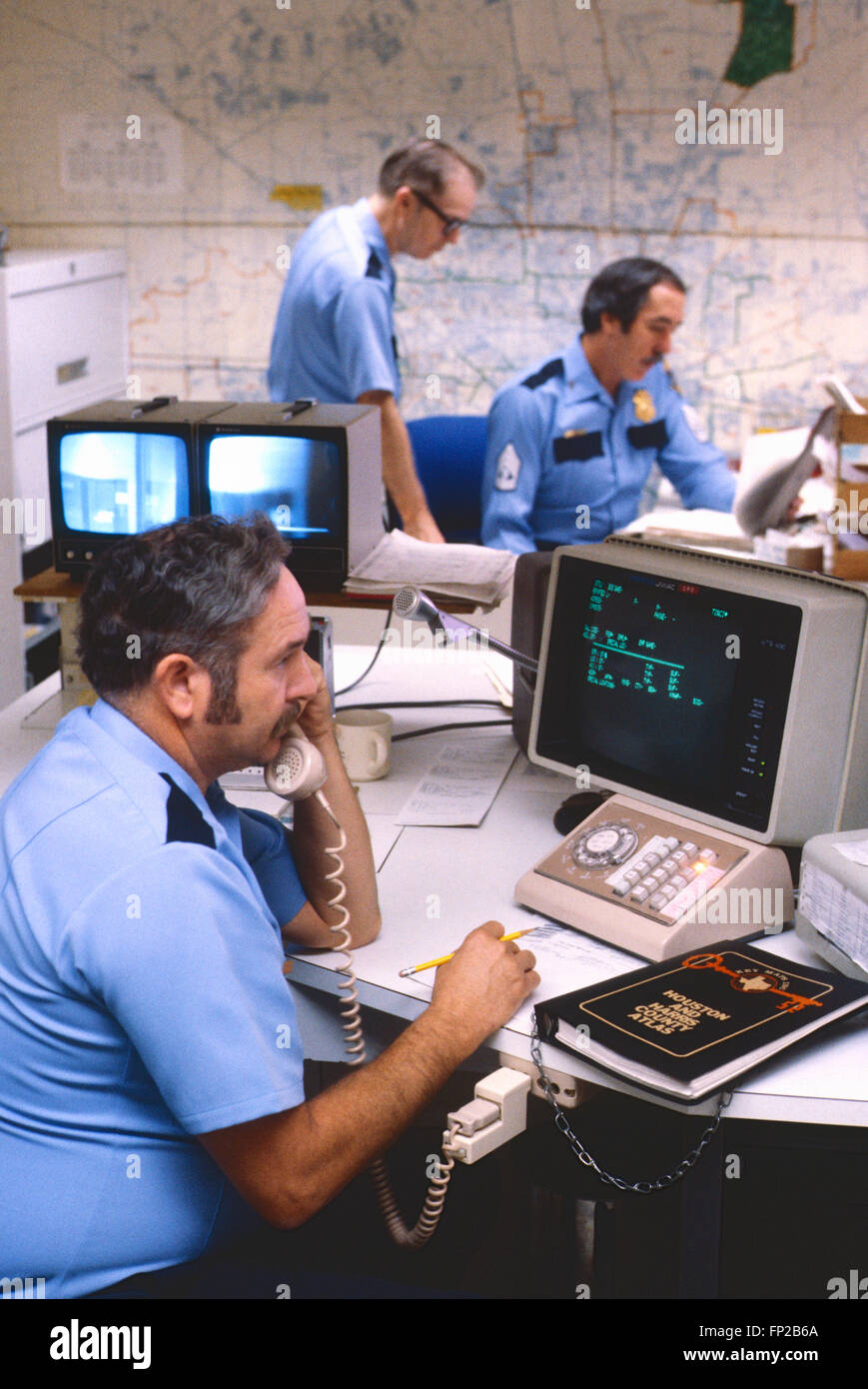 Houston Policeman at office computers and telephones - Stock Image