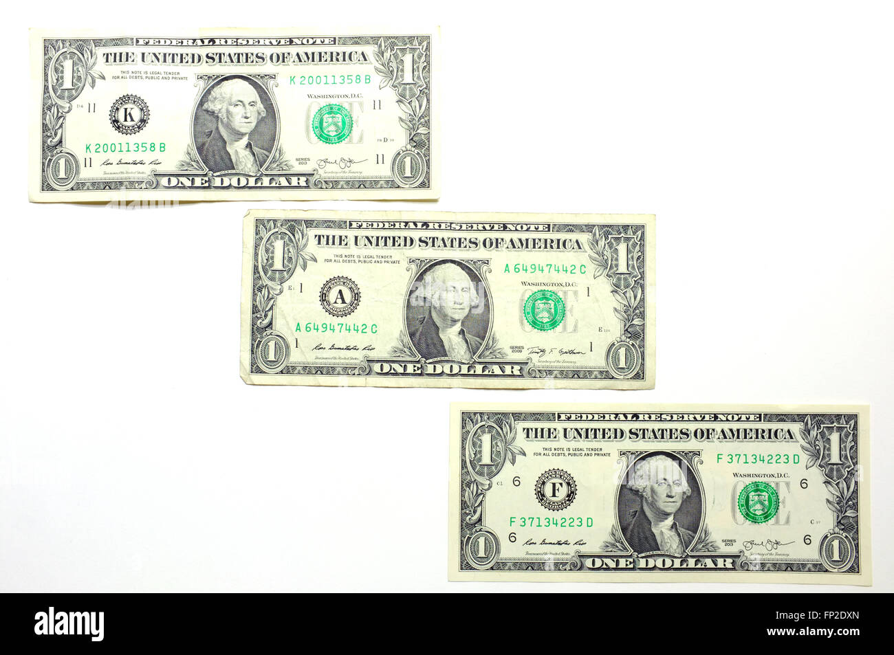 Three American One Dollar notes photographed against a white background - Stock Image