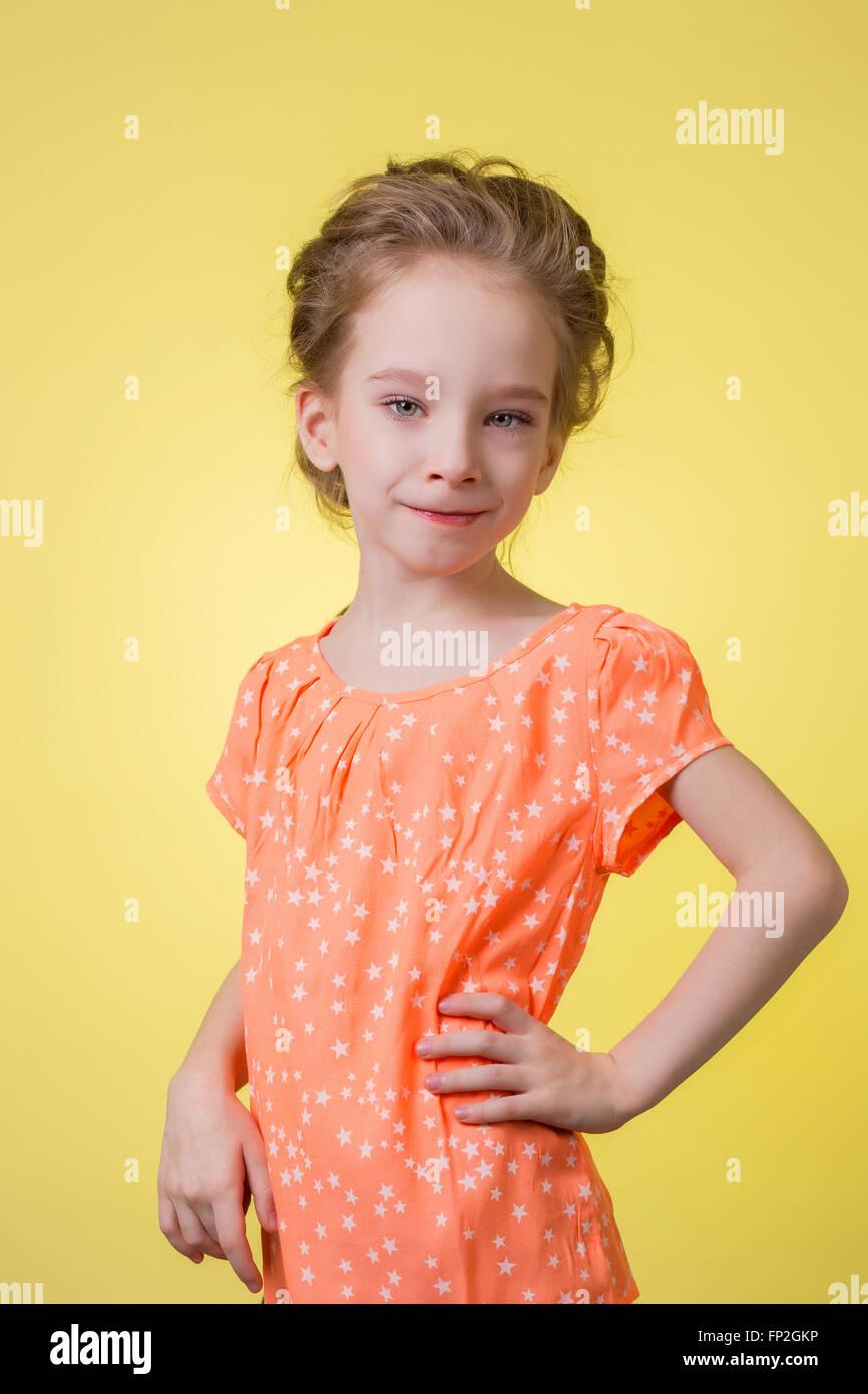 happy teen girl half length portrait isolated on yellow background - Stock Image