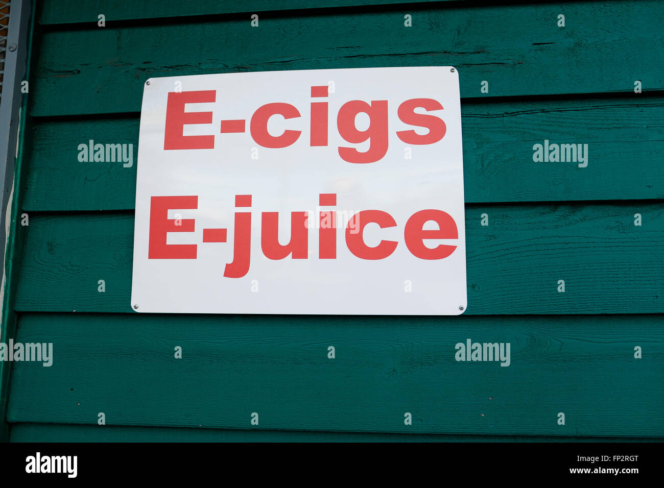Sign on a green building says e-cigs and e-juice showing customers what they sell at this new vaping store. - Stock Image