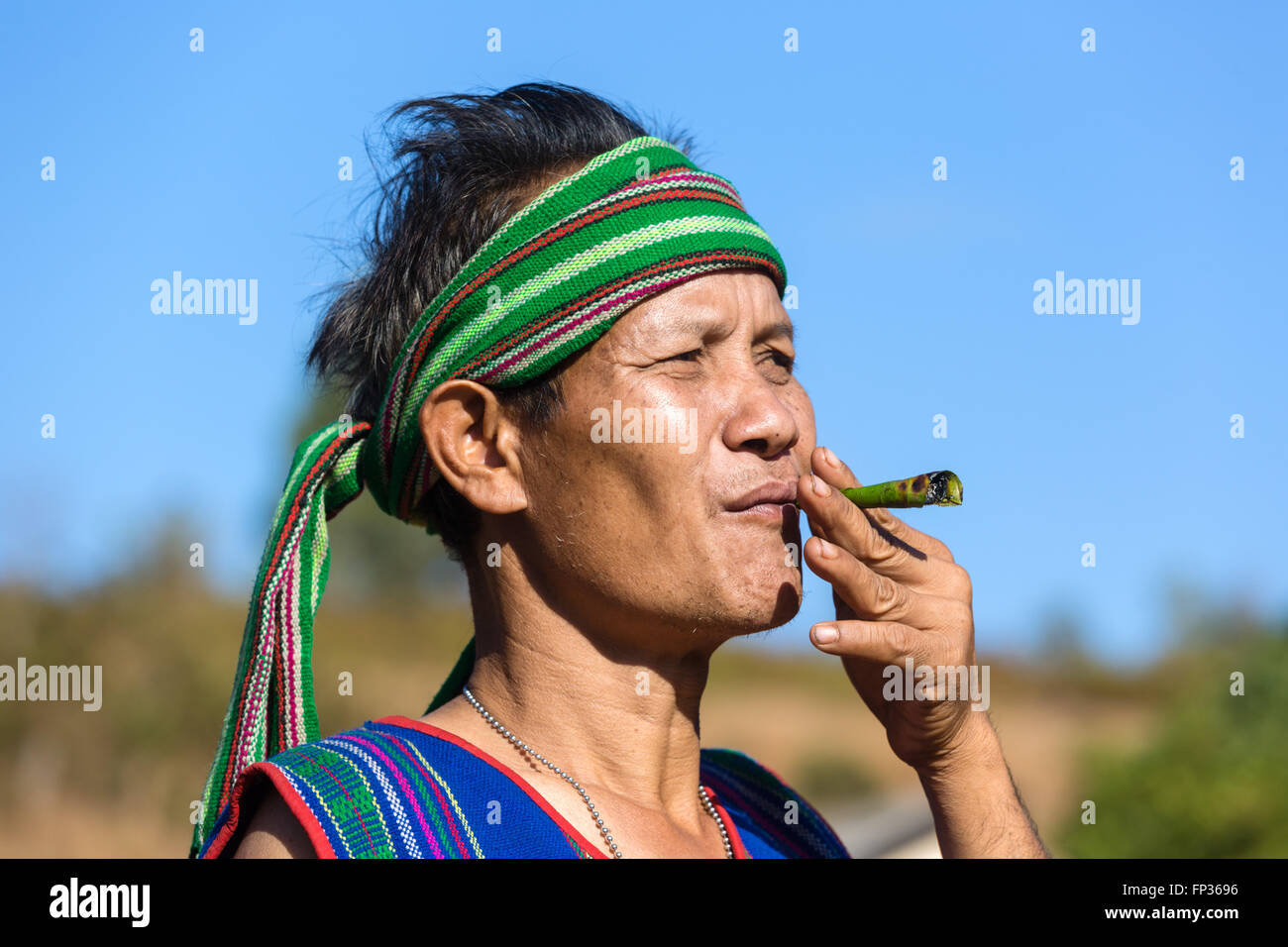 Man in traditional costume smoking cigar, Phnong tribe, ethnic minority, Pnong, Bunong, Senmonorom, Sen Monorom - Stock Image