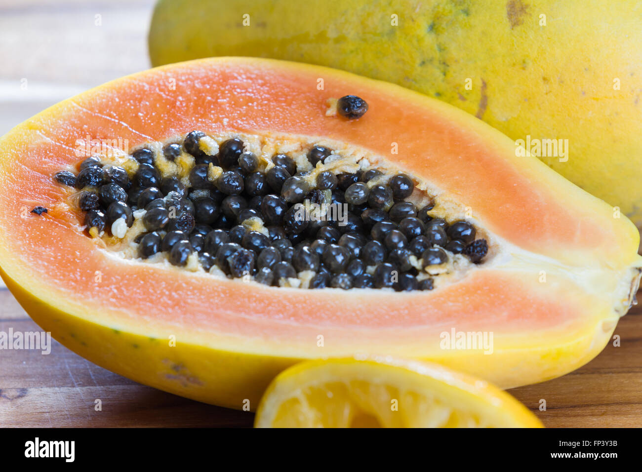 close up of a papaya cut in half revealing the meat and a pile of dark slimy seeds - Stock Image