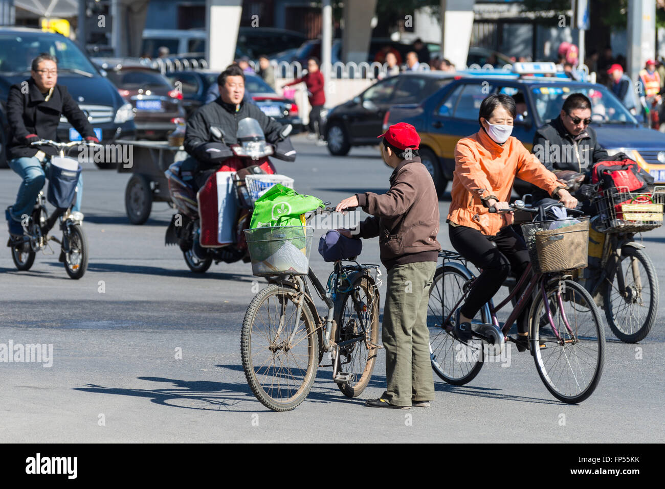 Bicyclists and bikers on the street in Beijing, China. Bicycles are a common form of transportation in the country. - Stock Image