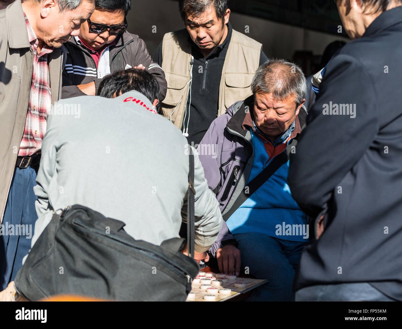 Senior men playing a game of Xiangqi, or Chinese chess, watched closely by others in the popular Temple of Heaven - Stock Image