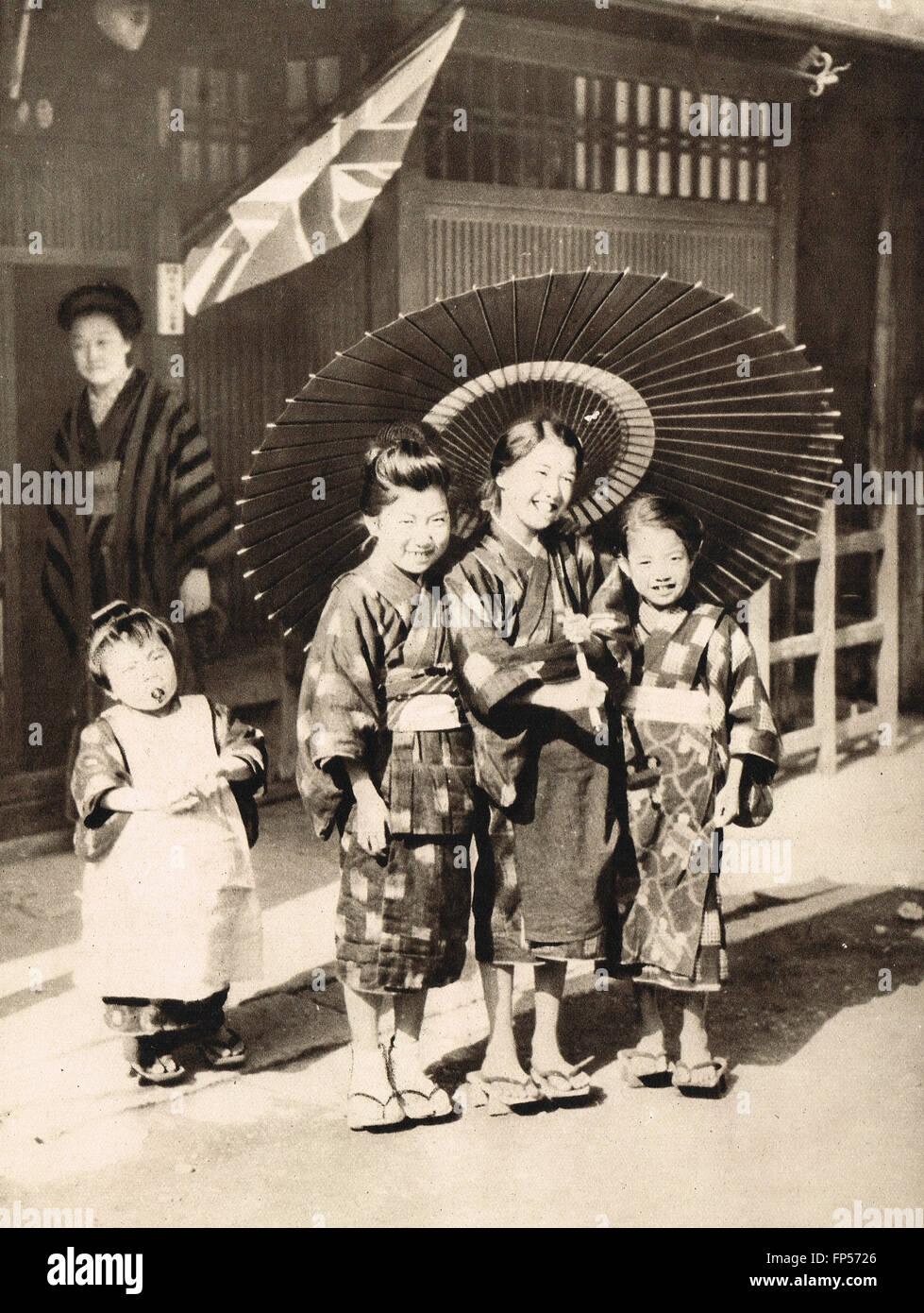 Smiling Japanese schoolgirls standing under union Jack. Royal visit of  Edward Prince of Wales the Future King Edward - Stock Image