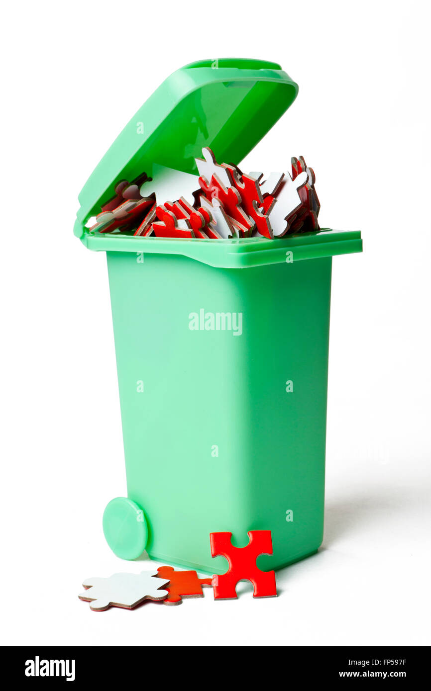 Garbage Can Full of Puzzles Pieces - Stock Image