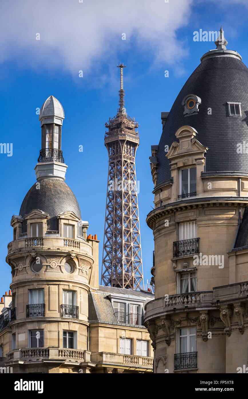 Top of the Eiffel Tower framed between towers of  Haussmannian buildings in the 16th Arrondissement. Paris, France - Stock Image