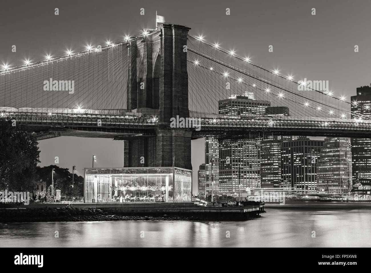 Brooklyn Bridge and carousel at twilight. New York City with Manhattan Financial District skyscrapers. Black & - Stock Image
