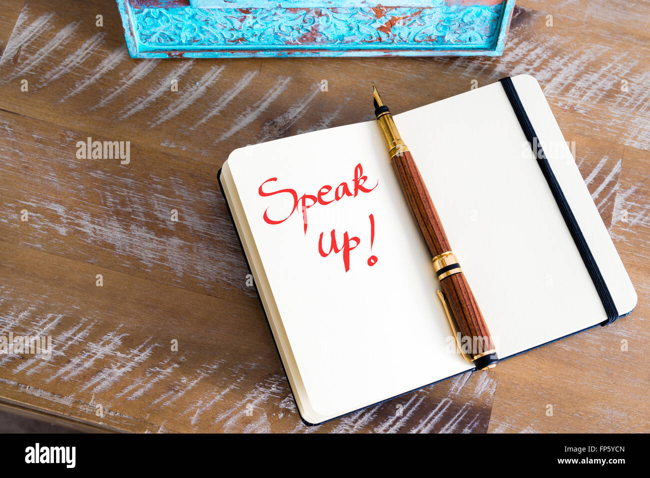Retro effect and toned image of a fountain pen on a notebook. Handwritten text Speak Up as business concept image - Stock Image