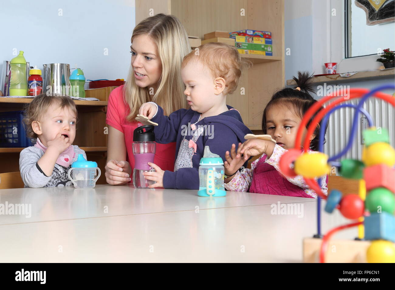 Some Kindergarten or nursery kidson a table drinking and playing - Stock Image