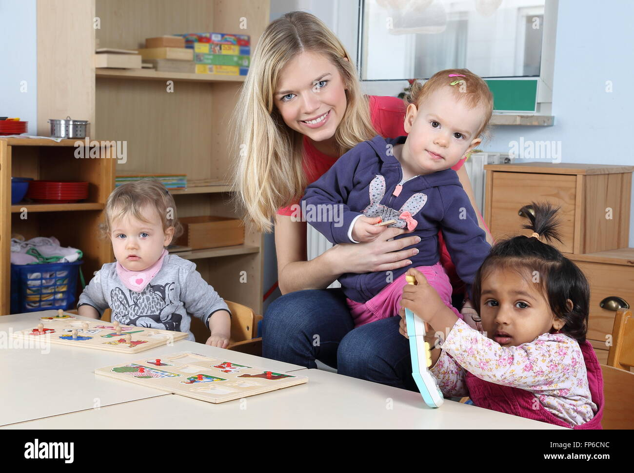 A Day care or kindergarten kids and teacher playing with a puzzle - Stock Image