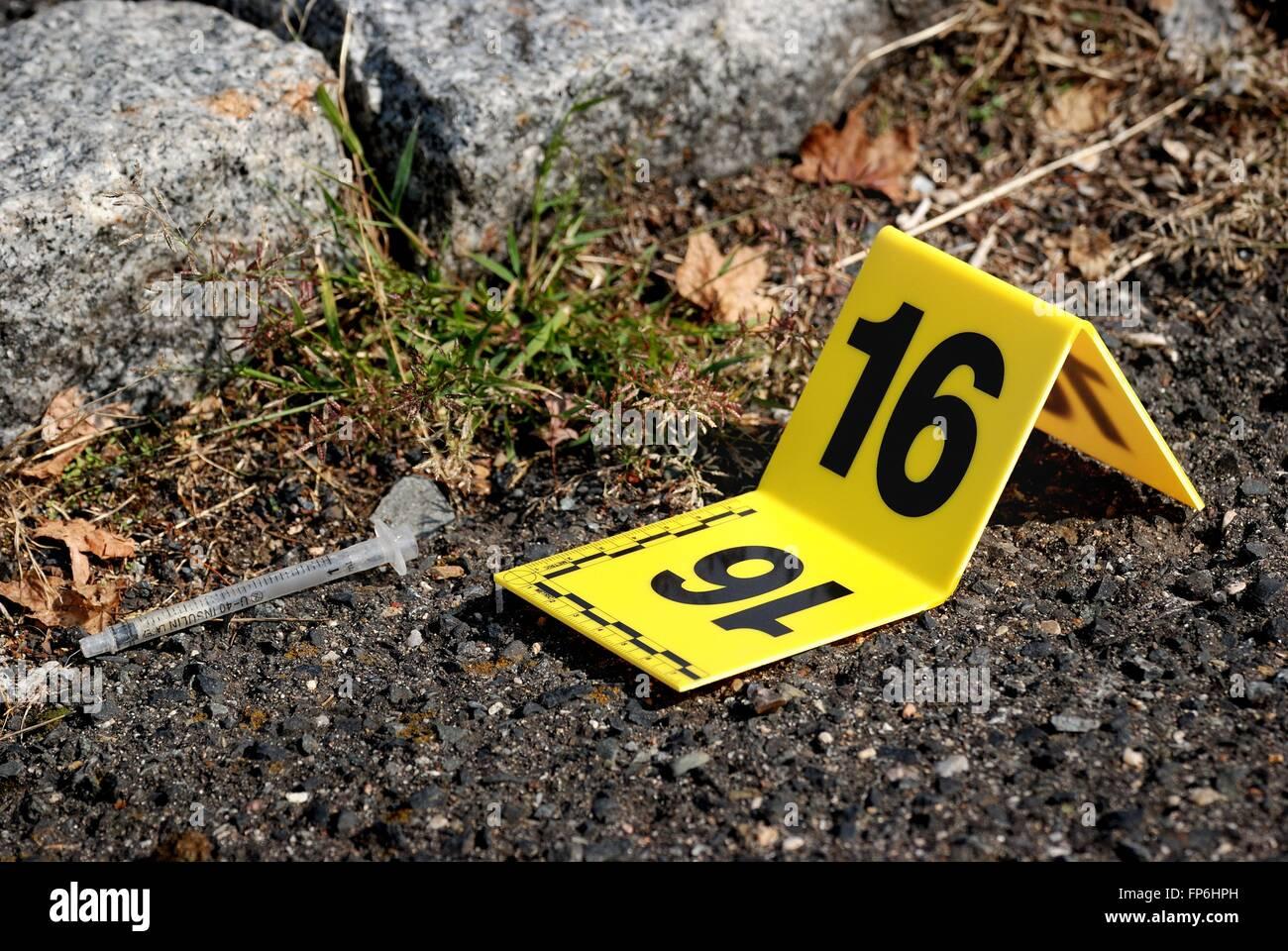 Crime Scene Evidence Marker Next to Syringe - Stock Image